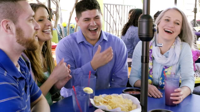 Happy friends laughing and having lunch at Mexican restaurant video