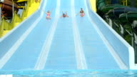 SLOW MOTION CLOSEUP: Happy friends sliding down extreme water slide toboggan smiling and screaming on sunny holidays in hot summer video
