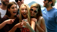 Happy friends watching a smartphone video