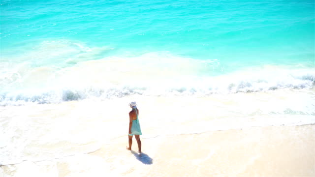 Happy girl at beach walking in shallow water. Top view on a woman on the white beach video