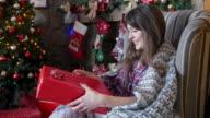 happy girl examines a gift near the Christmas tree video