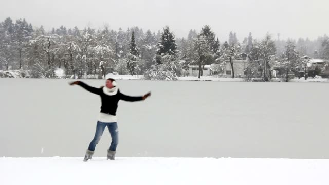 Happy girl playing in the snow by the lake video