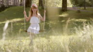SLO MO Happy girl swinging under a tree in nature video