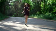 happy girl trips out on the road in the forest video