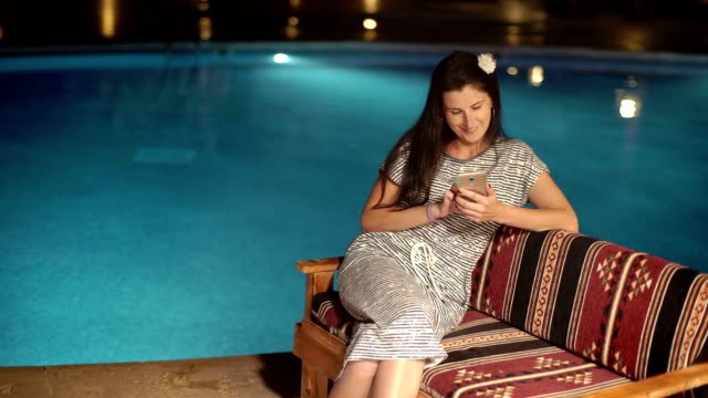 Happy girl using a smartphone, typing near swimming pool in the evening. video