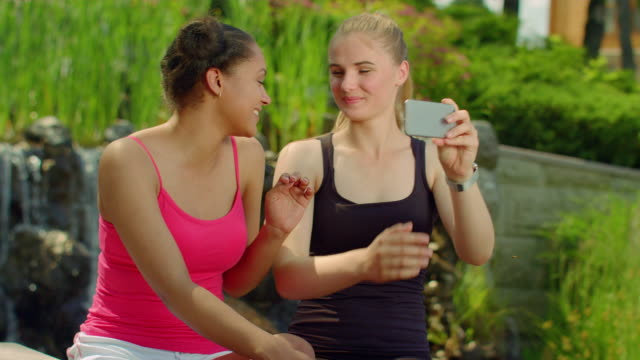 Happy girlfriends taking photo with smartphone in park. Selfie friends outdoors video