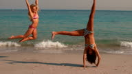 Happy girls doing a cartwheel on the beach video