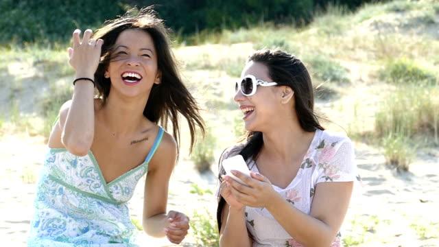 Happy girls take selfie on the beach- slowmotion video