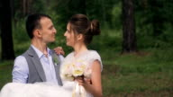 Happy groom holds on hands beautiful bride, close up video