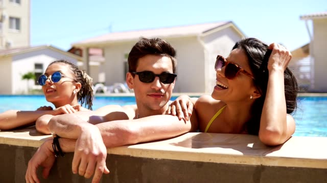 Happy group of friends enjoying summer pool party splashing their legs in the water. Young attractive people hanging out and chatting at the side of the pool in the summertime. video