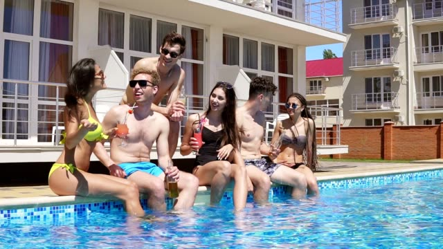 Happy group of young friends hanging out with coctails and chatting at the side of the pool in the summertime. Pool party. Slowmotion shot video
