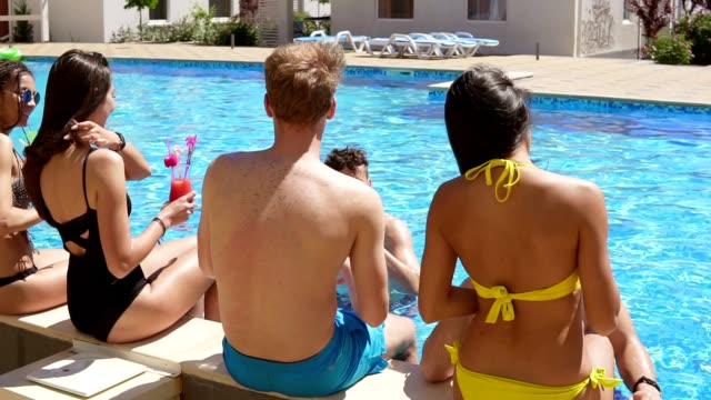 Happy group of young friends hanging out with coctails and chatting at the side of the pool in the summertime and dancing. Pool party. Slowmotion shot video