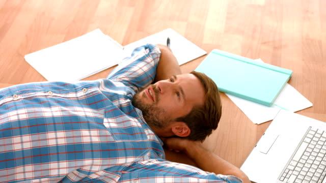 Happy handsome man lying on floor video
