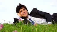 Happy handsome man lying on green grass video
