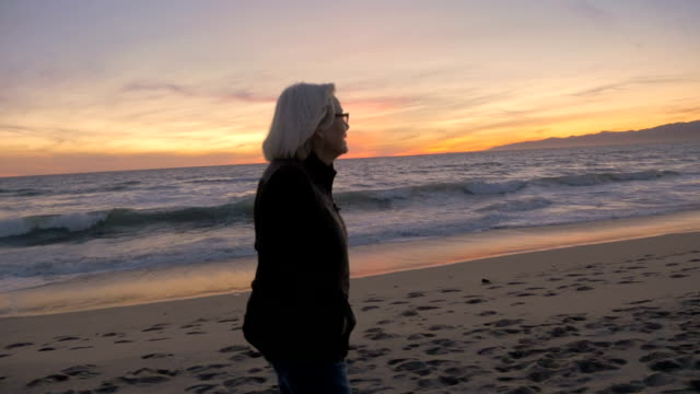 Happy healthy mature active retired woman looking at beach sunset video