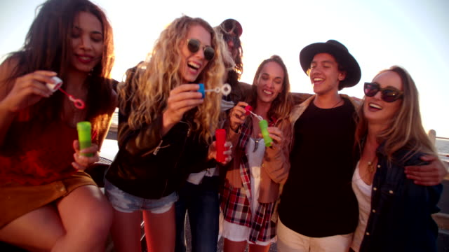 Happy hipster friend partying with bubbles outside at sunset video
