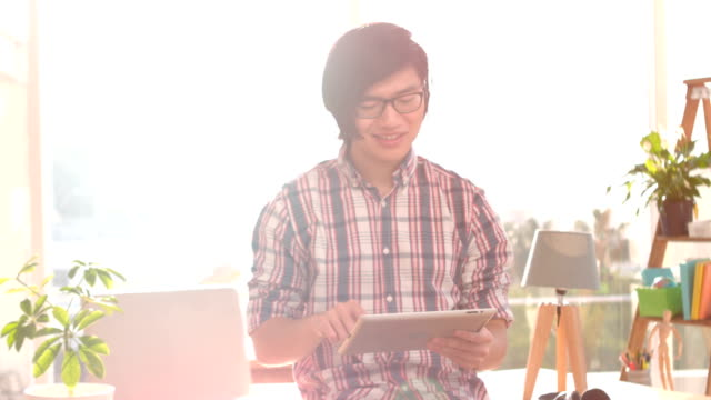 Happy hipster using his tablet pc video