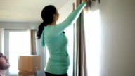 Happy Hispanic couple hanging curtains in new home after moving in video