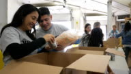 Happy Hispanic couple sorting donations with diverse group of volunteers video
