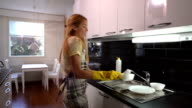 Happy housewife washing the dishes and dancing in the kitchen. Slow Motion. video
