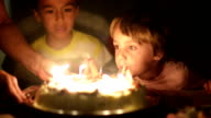 Happy kid blowing candles at his anniversary video