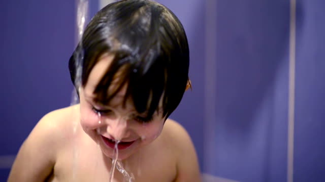 Happy kid in bathroom playing with water video