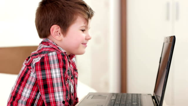 happy kid skyping via laptop, smiling child at home, little boy watching funny cartoons at gadget video