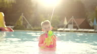 SLOW MOTION: Happy kid squirting water drops with water gun directly into camera at beautiful golden summer sunset in fun aqua park video