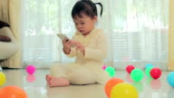 Happy little asian girl using mobile phone in the home video