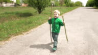 Happy little boy plays with rod walks outdoor road video