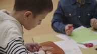 4K: Happy Little Boy using scissors in kindergarten. video