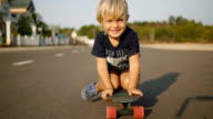 Happy little child rides sitting on skateboard in slowmotion. video