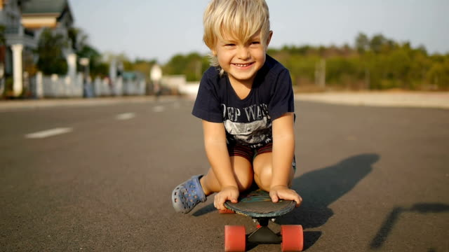 Happy little child rides sitting on skateboard in slowmotion. video