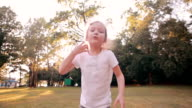 Happy little girl cheerfully jumps, blows kisses in front of camera in the nature. Beautiful sunset light. Slow mo video
