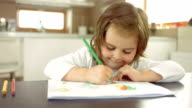 Happy Little Girl Drawing Behind A Table video