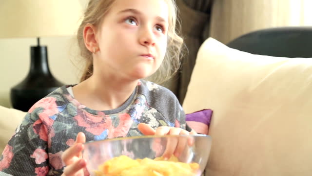 Happy little girl eating potato chip video