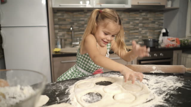 Happy little girl having fun with dough and making round shaped cookies with drinking glass. video