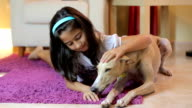 Happy little girl petting her dog at home video