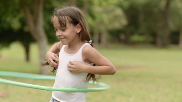 Happy little girl playing with hula hoop in park video