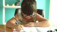 Happy little girl reading and write a book on the table. video