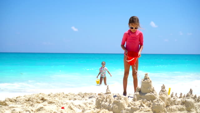 Happy little kids playing with beach toys during tropical vacation video