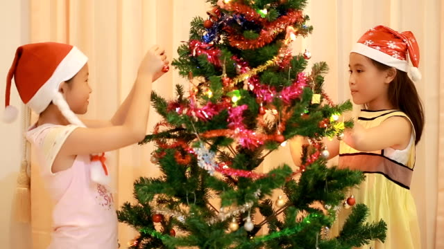 Happy little sisters decorate christmas tree video