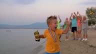 Happy little winner running with trophy video