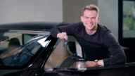 Happy man hold a keys from electric car video