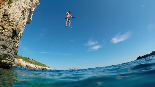 SLOW MOTION UNDERWATER: Happy man jumping off a high ocean cliff into sea water video