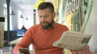 Happy man reading daily newspaper, aswer phone call, portrait, cafe, steadicam video