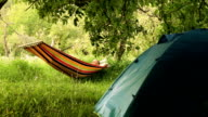 Happy man relaxing in hammock in Summer camp video