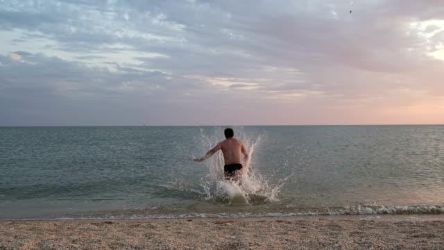 Happy man running in to sea to swim video