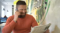 Happy, man talking by smartphone, looking at camera, portrait, cafe, steadicam video