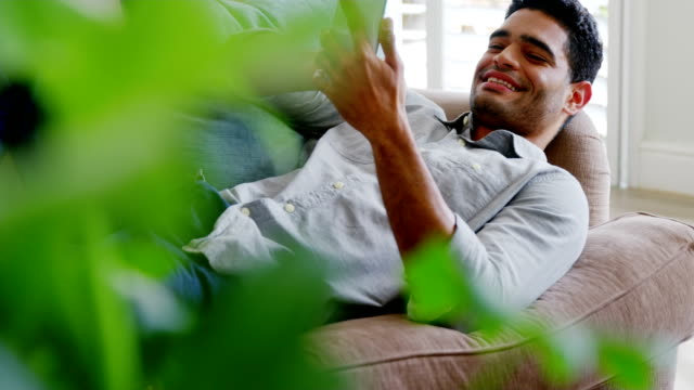 Happy man using mobile phone in living room video